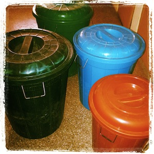 Koleksi gentong aneka ukuran (50-100 liter) yang sekarang penuh air dan memenuhi lorong rumah. *Berat mau angkat ke kamar mandi & dapur*